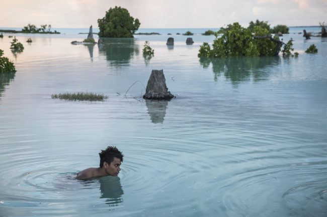 Peia Kararaua, 16, swims in the flooded area of Aberao village that is located in Tarawa atoll, Kiribati, in the Pacific Ocean. Kiribati is one of the countries most affected by sea level rise due to the climate change. During high tide many villages become inundated making large parts of them uninhabitable. Photo by Vlad Sokhin, @lens_pacific
